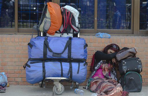 An Indian tourist sleeps at the Nepal International airport as she waits to be evacuated in Kathmandu, Nepal, Monday, April 27, 2015.  (AP Photo/Manish Swarup)