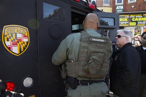 Gov. Larry Hogan, R-Md., talks with Maryland State Police as he tours damage after an evening of riots following the funeral of Freddie Gray on Tuesday, April 28, 2015, in Baltimore. (AP Photo/Evan Vucci)