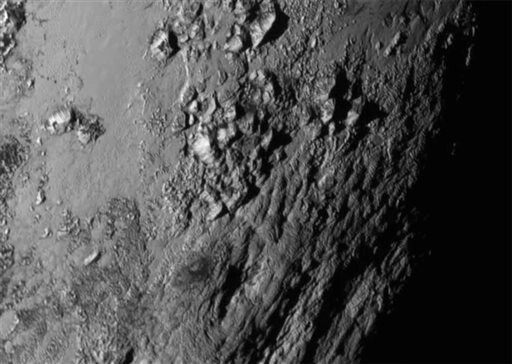 This Tuesday, July 14, 2015 image provided by NASA on Wednesday shows a region near Pluto's equator with a range of mountains captured by the New Horizons spacecraft. (NASA/JHUAPL/SwRI via AP)