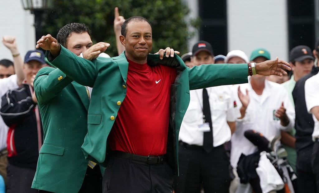 5410b8a12f1f2 Patrick Reed helps Tiger Woods with his green jacket after Woods won the  Masters golf tournament Sunday